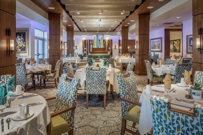 Dining room tables set for dinner service at All Seasons Naples in Naples, Florida