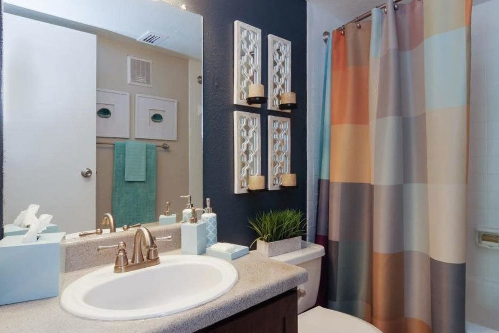 Model bathroom with large vanity mirror and oval tub and shower combo at Vantage Point in Houston, Texas