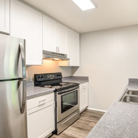 Kitchen area with white cabinets at Hillside Terrace Apartments in Lemon Grove