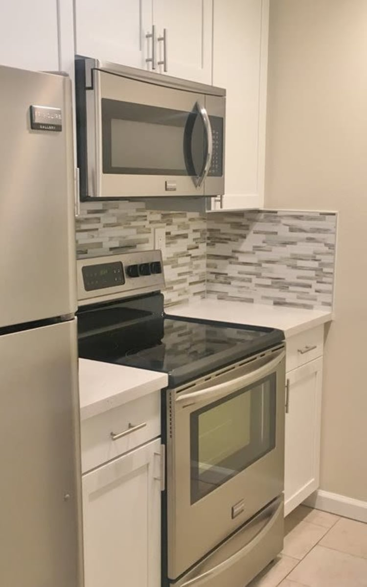Kitchen with white cabinetry and stainless-steel appliances at Haven Warner Center in Canoga Park, California