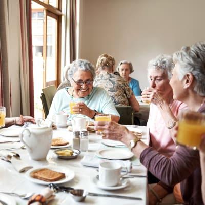 Residents sitting in a sunlit cafe eating breakfast at Arbor Glen Senior Living in Lake Elmo, Minnesota