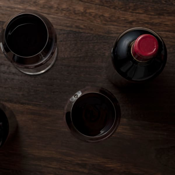 Red wine in glasses and a sealed bottle on a walnut counter in Redwood City, California