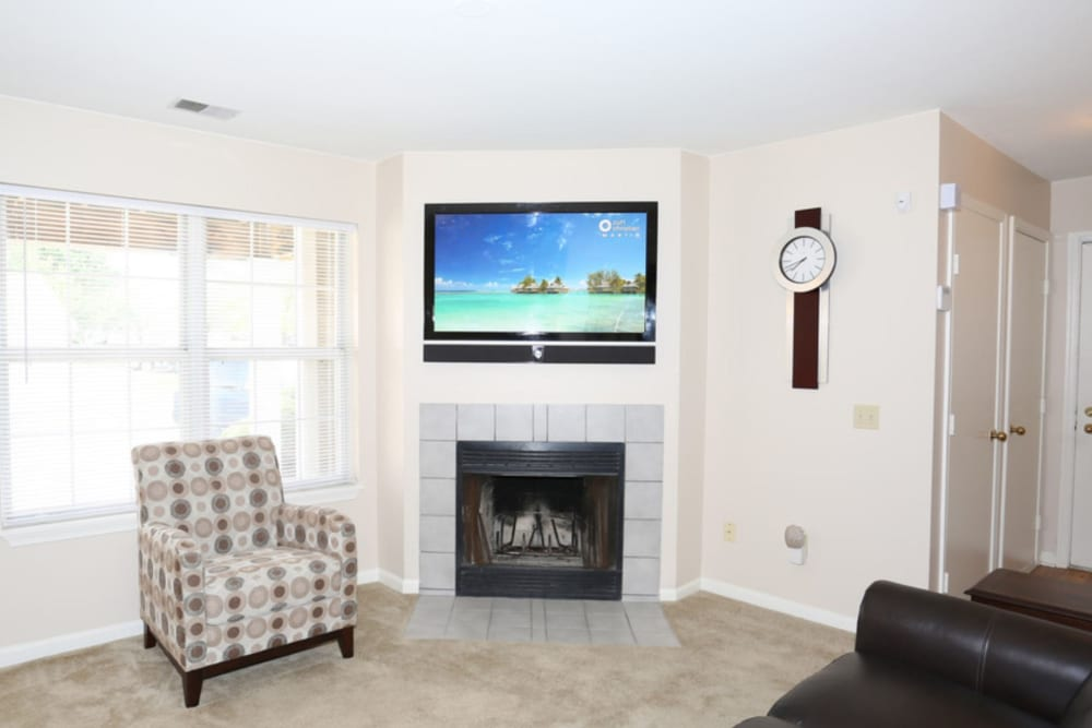 Living room with fireplace at Bennington Hills Apartments in West Henrietta, New York