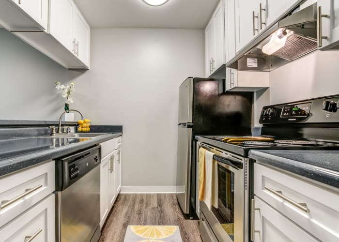 White renovated Kitchen with stainless steel appliances at The Timbers Apartments in Hayward, CA