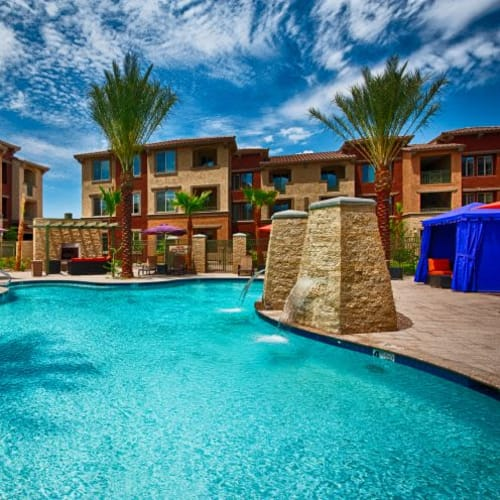 Resort-style swimming pool with private cabanas nearby at Elevation Chandler in Chandler, Arizona