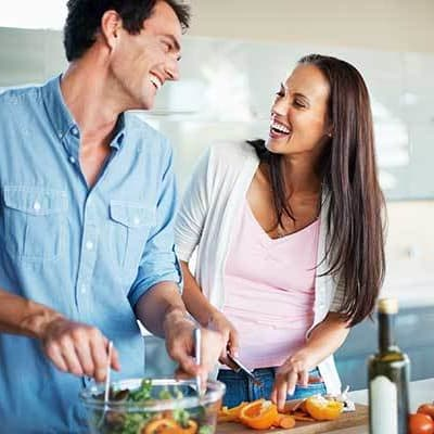 A happy couple cooking dinner at Ellison Heights Apartments in Rochester, New York