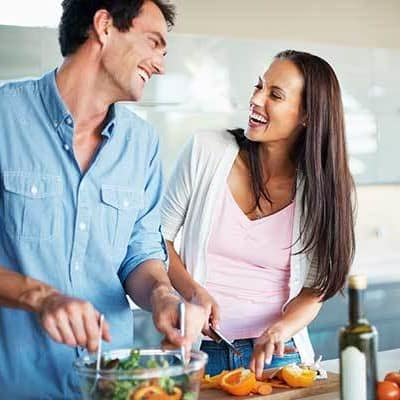 A happy couple cooking dinner at Ellison Heights Apartments in Rochester, NY