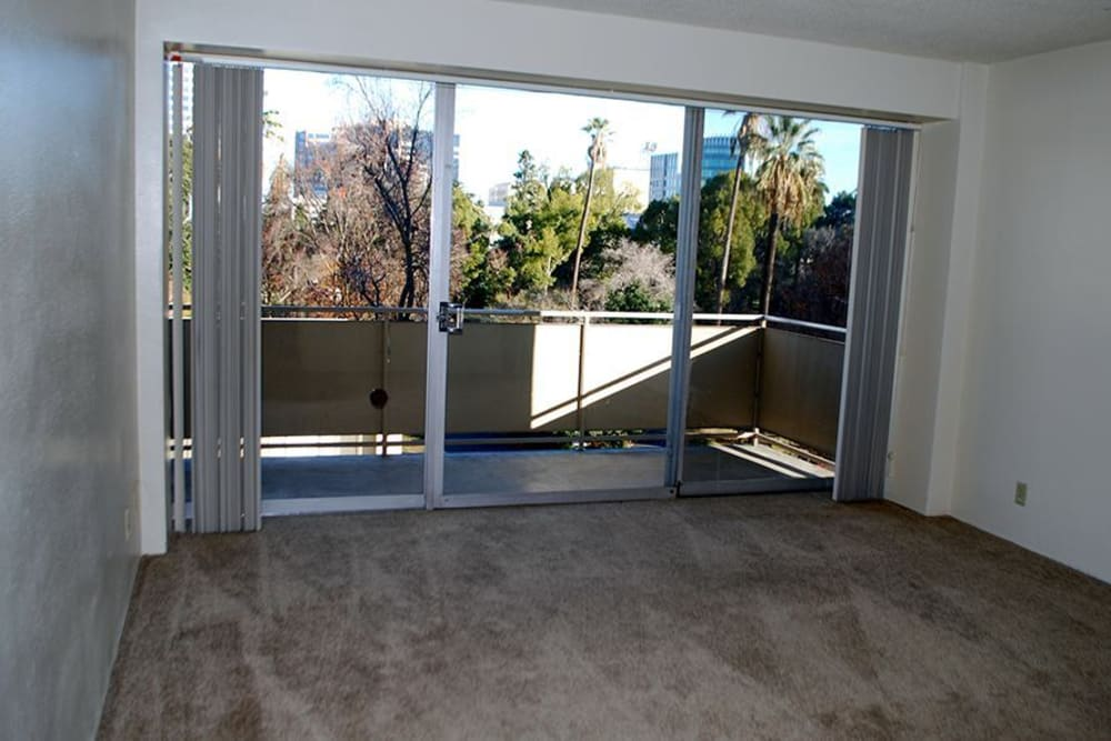 Bright living room with sliding door to balcony at Park Place Senior Living in Sacramento, California