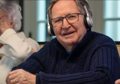 Senior listening to headphones at a Maplewood Senior Living community