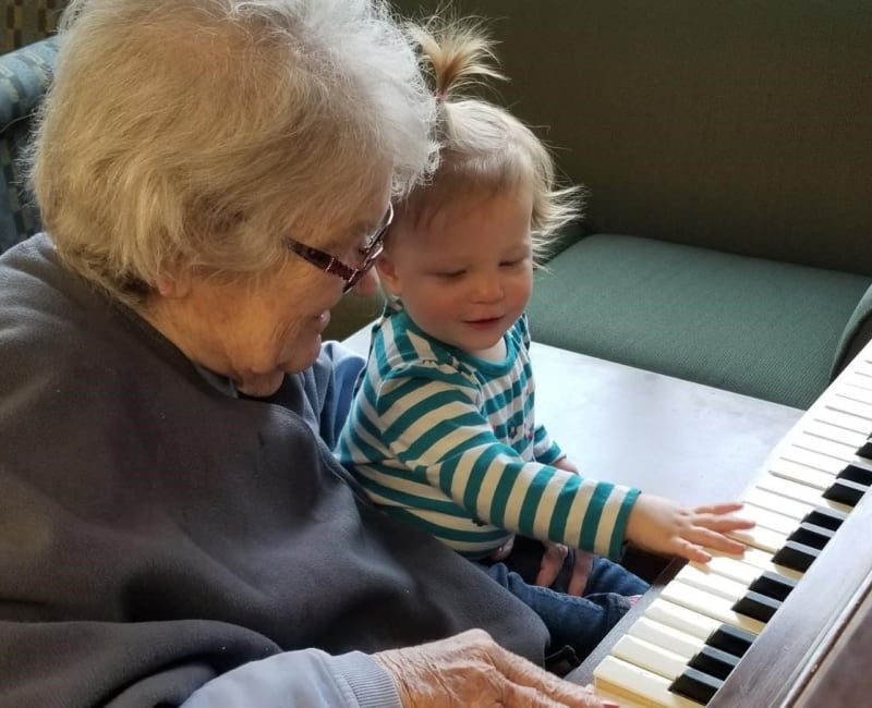 A resident shows her young visitor how to play a piano at Ebenezer Ridges Campus in Burnsville, Minnesota