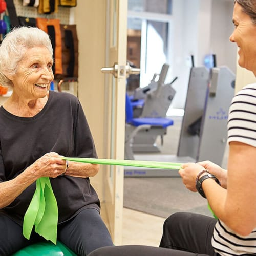 Resident exercising with personal trainer at Celebration Village Forsyth in Suwanee, Georgia