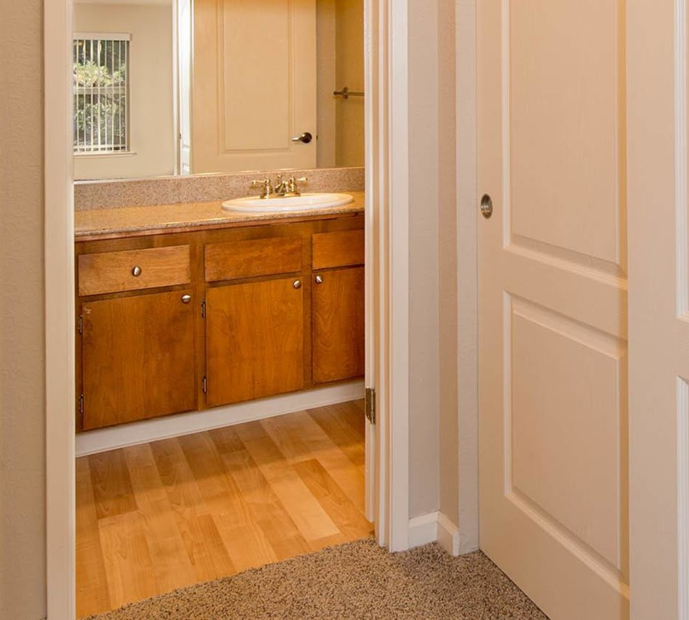 Master bathroom with a large vanity mirror at Seventeen Mile Drive Village Apartment Homes in Pacific Grove, California