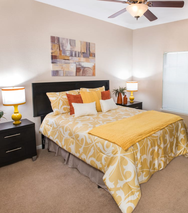 Model bedroom with a ceiling fan at Crescent Cove at Lakepointe