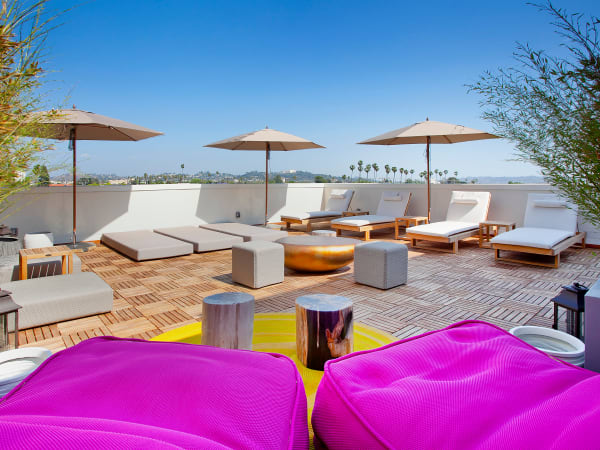 Roof top lounge with umbrellas at Brio Apartment Homes in Glendale, California