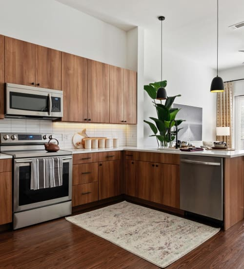 Modern kitchen with stainless-steel appliances and quartz countertops in a model apartment at 4600 Ross in Dallas, Texas