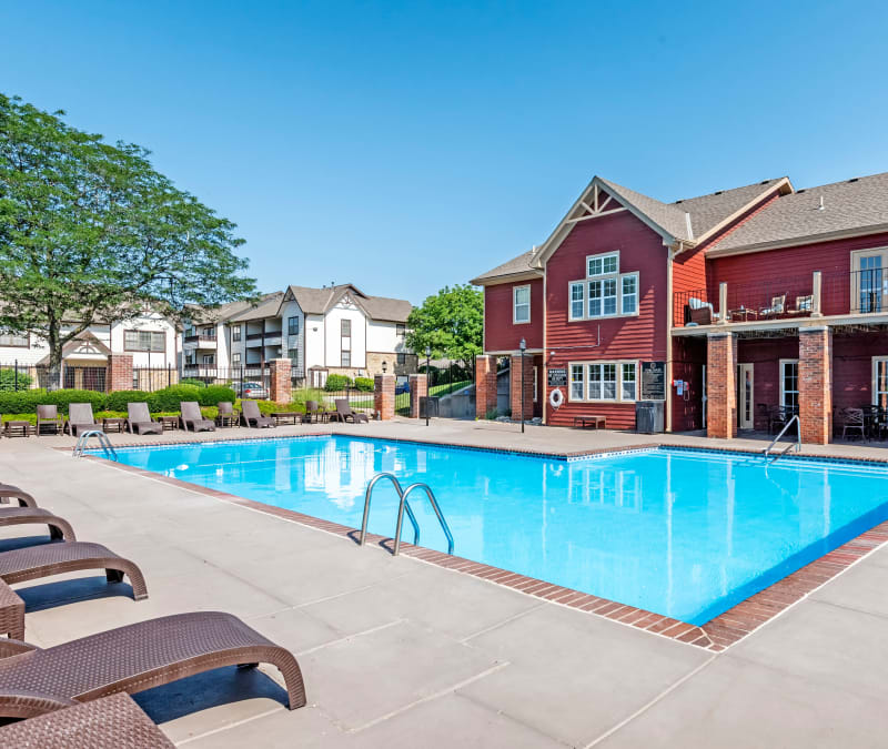 Sparkling swimming pool with lounge chairs at Coach House Apartments in Kansas City, Missouri