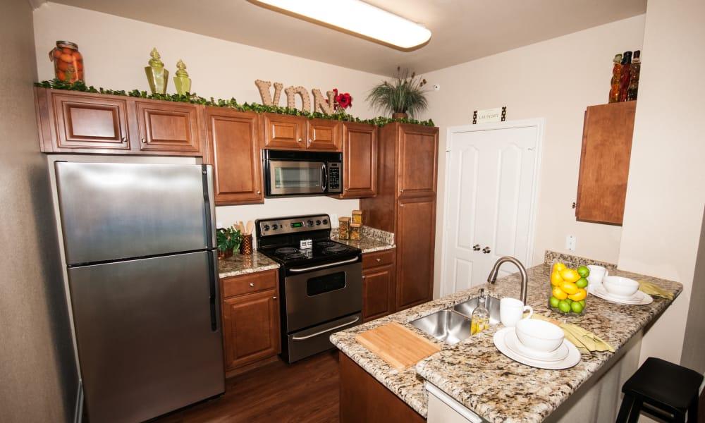 Plank flooring and granite countertops in a kitchen at Villas of Vista Del Norte in San Antonio