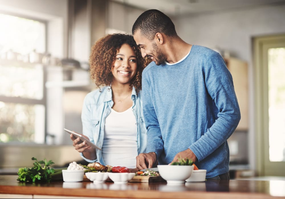 Resident couple cooking a fresh meal in the gourmet kitchen of their new home at Sofi Berryessa in San Jose, California