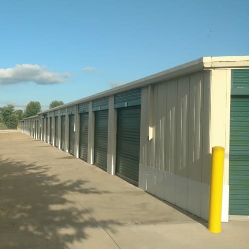 Outdoor storage units with green doors at Red Dot Storage in Bloomington, Illinois