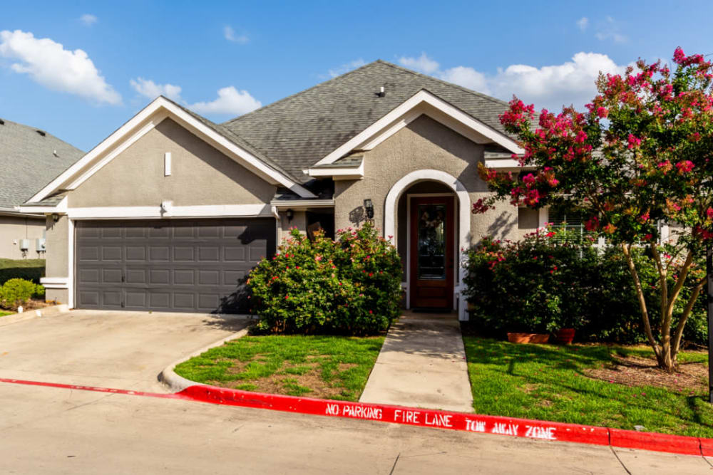 Unit entrance with two-car garage and landscaping at Marquis at Stone Oak in San Antonio, Texas