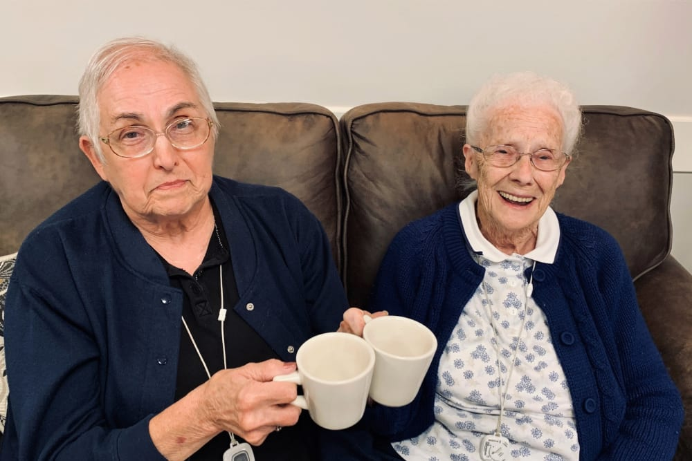 Resident friends give a toast with their coffee cups at Corridor Crossing Place in Cedar Rapids, Iowa