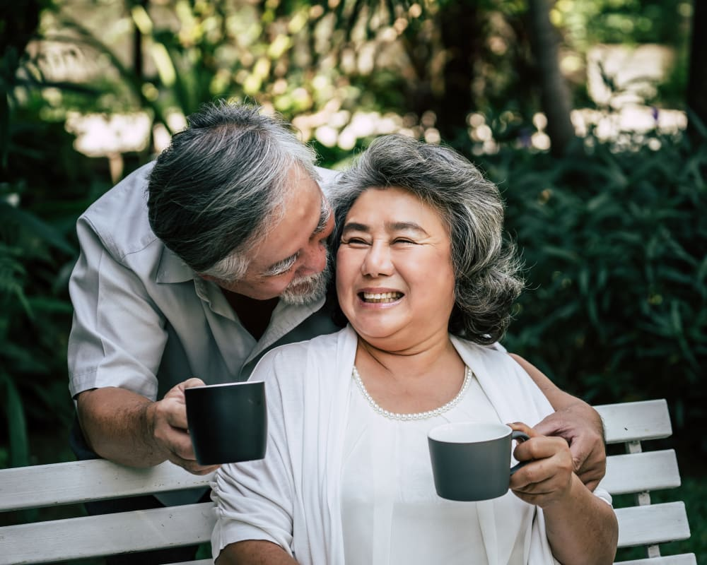 Resident couple enjoys coffee outside at Arlington Place of Red Oak in Red Oak, Iowa.