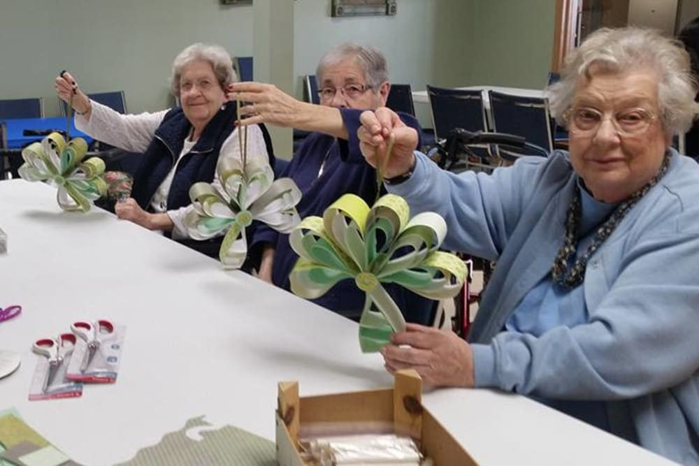 Residents showing off craft projects at Prairie Meadows Senior Living in Kasson, Minnesota.