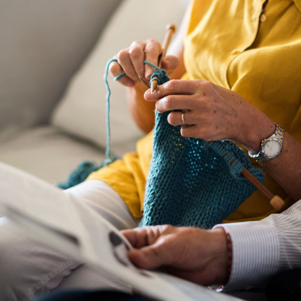 Resident knitting on a couch in a Randall Residence community