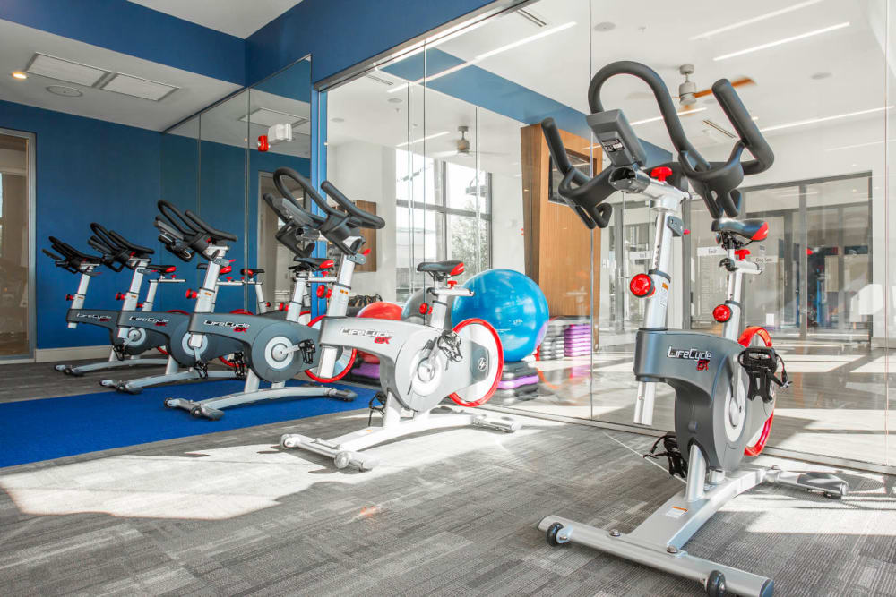 Five spin cycles lined up against mirror in fitness room at Marq Midtown 205 in Charlotte, North Carolina