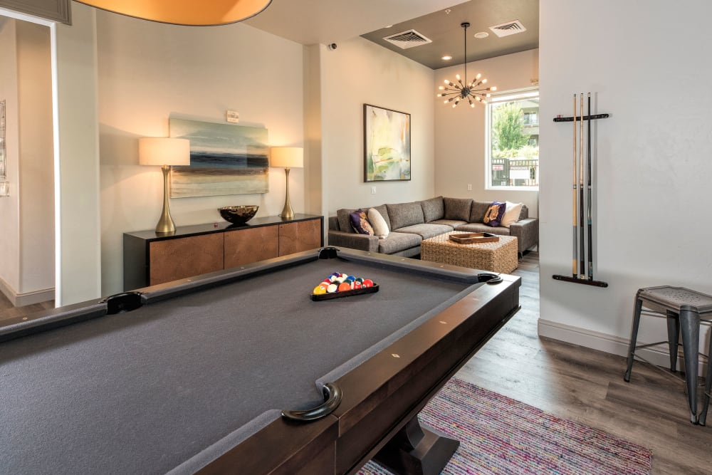 Resident clubhouse with a pool table and comfortable seating for entertaining guests at The Artisan Apartment Homes in Sacramento, California