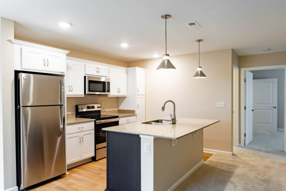 Kitchen with hanging lights at Bennington Hills Apartments in West Henrietta, New York