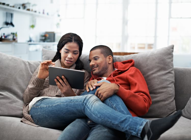 Young couple using their tablet while sitting on the sofa at Warner Village Apartments home in Trenton, New Jersey