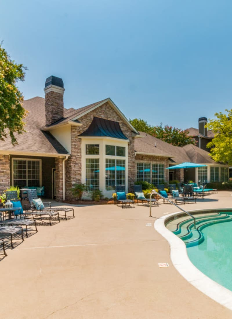 Poolside walk area with lounge chairs and umbrellas at Marquis at Carmel Commons in Charlotte, North Carolina