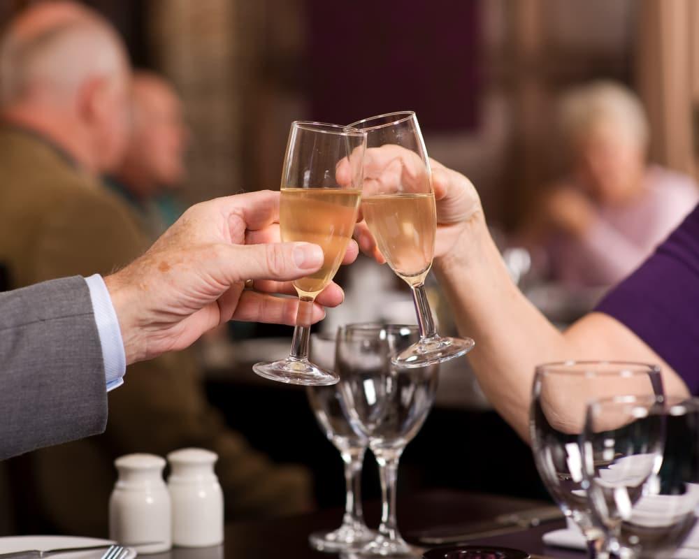 Happy seniors drinking wine at Hillcrest of Loveland in Loveland, Colorado