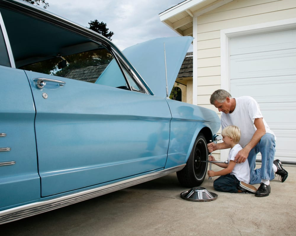 Father and son working on classic car being stored at STOR-N-LOCK Self Storage in Boise, Idaho
