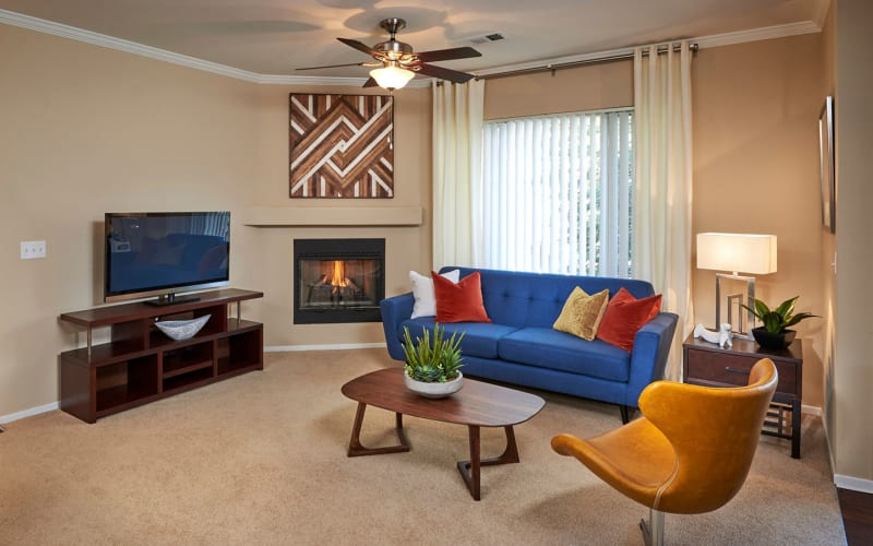 Spacious living room with a fireplace at Legend Oaks Apartments in Aurora, Colorado
