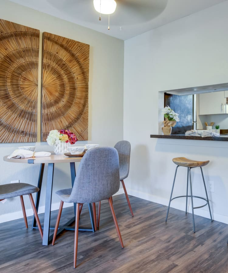 Dining room with a ceiling fan and wood-style flooring in a model home at Haven Martinez in Martinez, California
