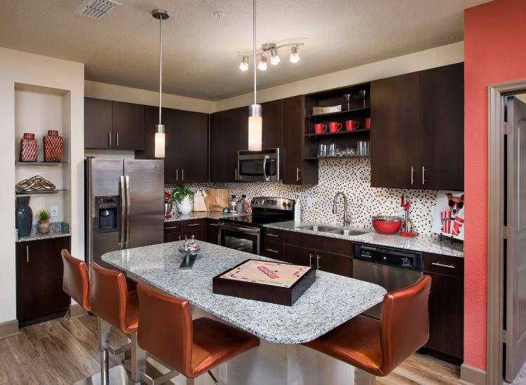 Modern kitchen with granite countertops and dark wood cabinetry in a model home at The Courtney at Universal Boulevard in Orlando, Florida
