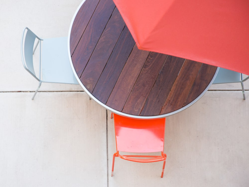 Overhead view of an umbrella providing shade for a table and chairs at Sofi Belmont Glen in Belmont, California