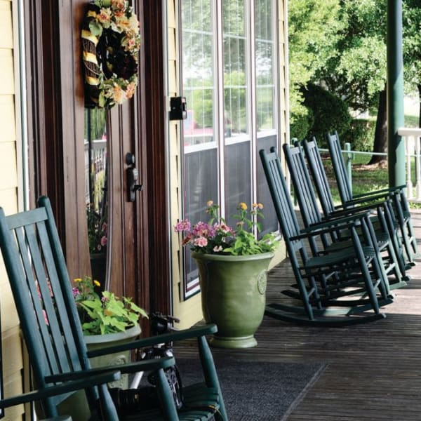 Front porch with a row of seats at Quail Park of Granbury in Granbury, Texas