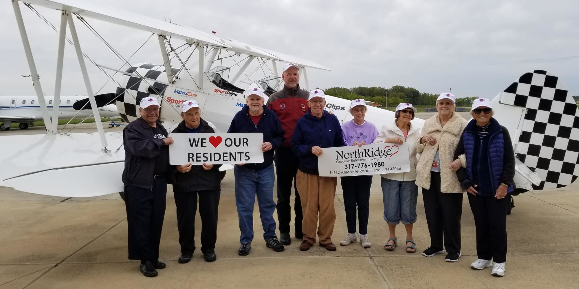 Residents from Northridge Gracious Retirement Living in Fishers, Indiana holding signs in front of a plane