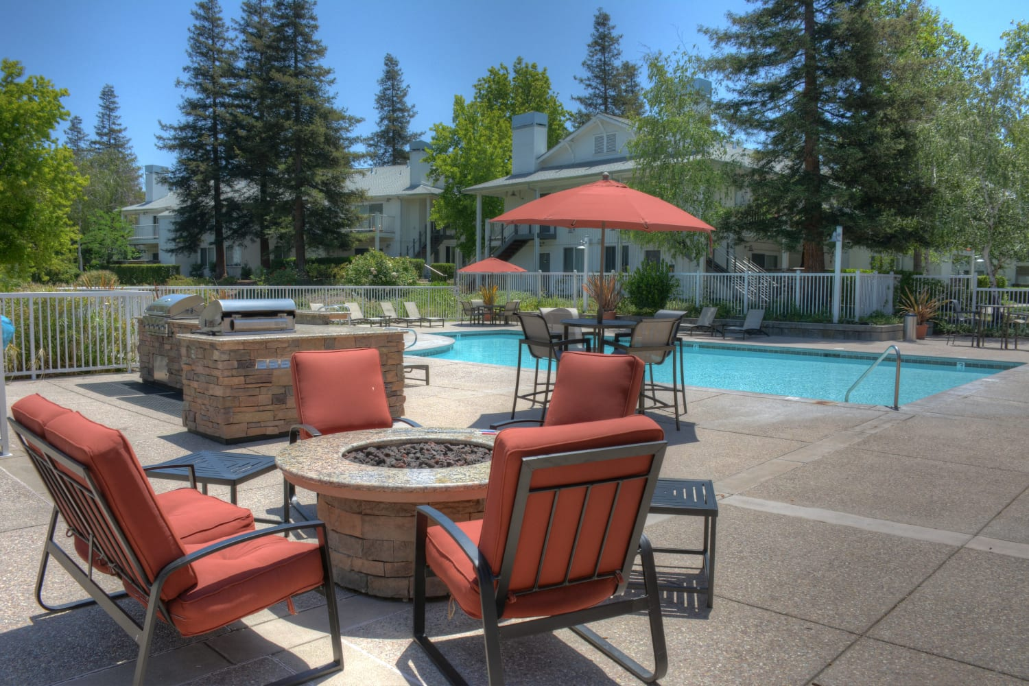 Fire pit and seating near swimming pool at Cotton Wood Apartments in Dublin, California