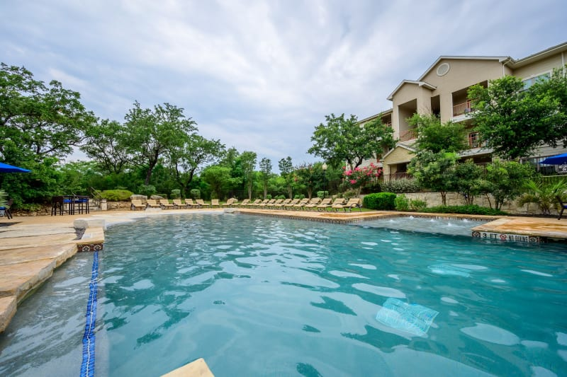 Poolside lounge chairs at Pecan Springs Apartments in San Antonio, Texas