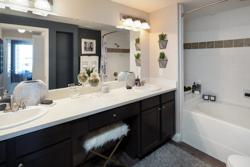 Model bathroom with large vanity mirror and oval tub at The Retreat at Cinco Ranch in Katy, Texas