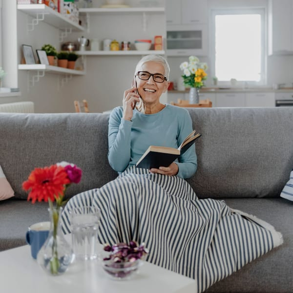 A resident sitting in her cozy apartment at Pacifica Senior Living Menifee in Sun City, California.