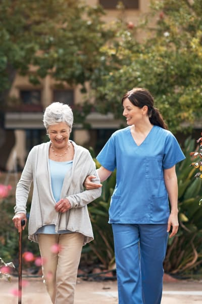Nurse walking with a resident outside at a Living Care Lifestyles community