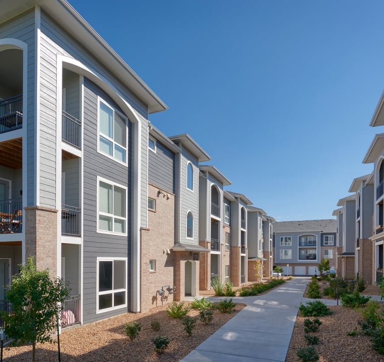 Exterior photo of homes and a walking path at Hawthorne Hill Apartments in Thornton, Colorado