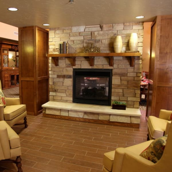 Warmly lit lounge with a fireplace at Quail Park Memory Care Residences of Visalia in Visalia, California