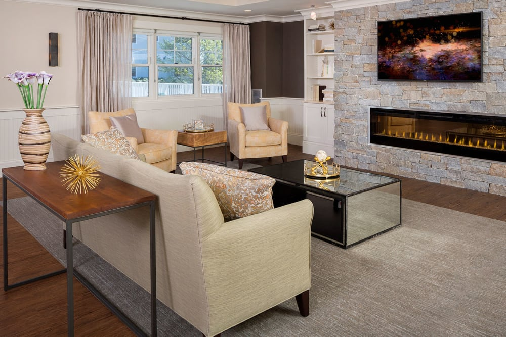 Seating in the clubhouse with a beautiful fireplace at Maplewood at Weston in Weston, Massachusetts