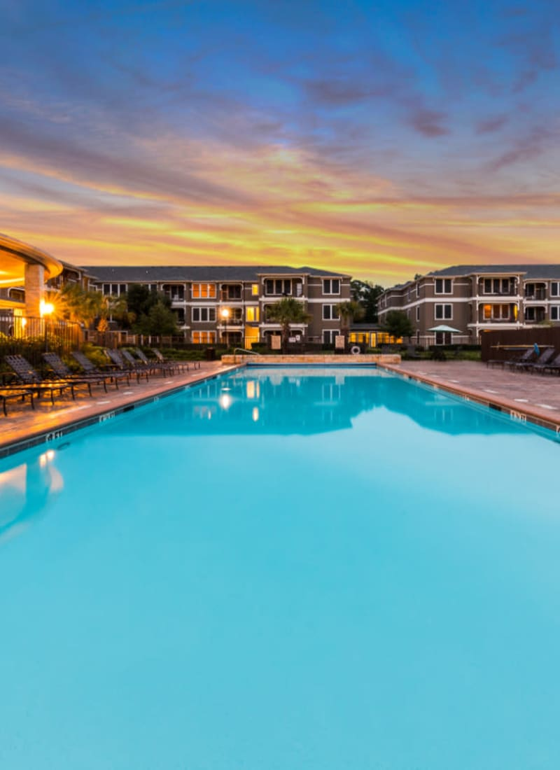 Lighted pool at sunset overlooking units at Marquis at The Cascades in Tyler, Texas